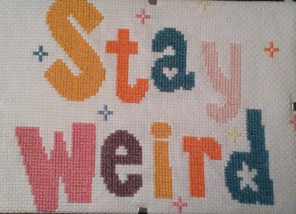 """Multicolored cross-stitch that reads """"Stay Weird"""""""